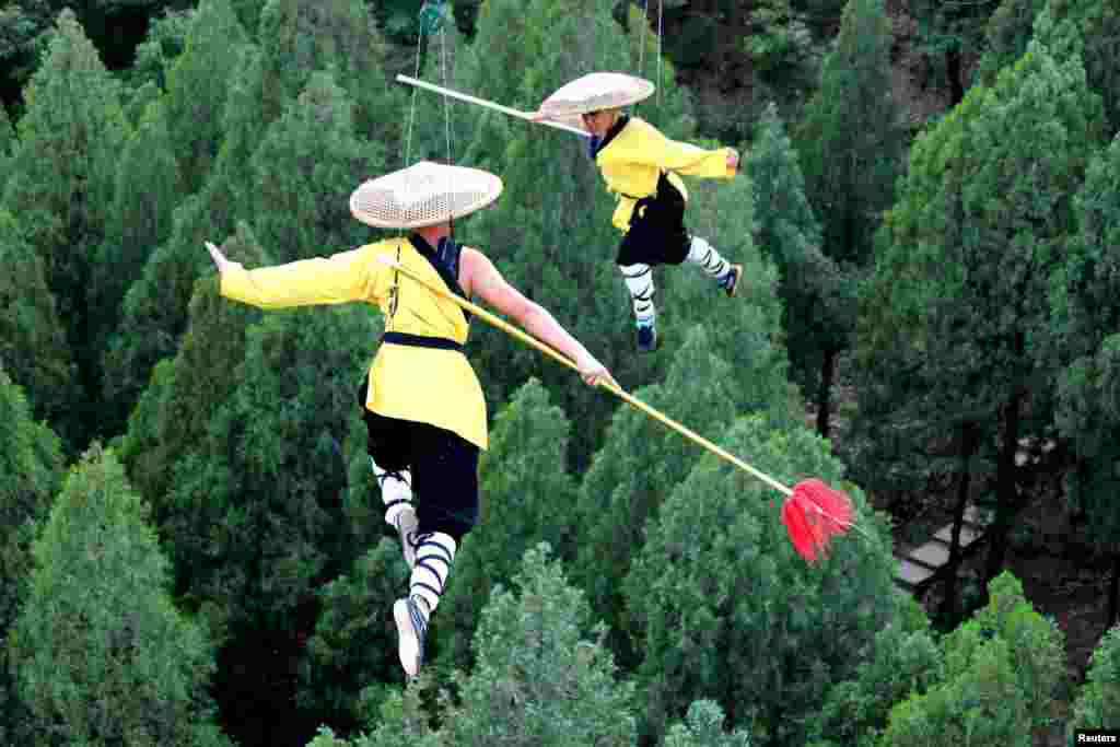 Shaolin martial arts students perform Kung Fu on suspended wires in a rehearsal for a live-action night show in Zhengzhou, Henan province, China, April 28, 2018.