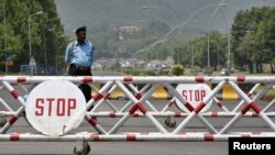 FILE - A policeman stands behind a barrier on the road leading toward the Diplomatic Enclave in Islamabad, Pakistan.