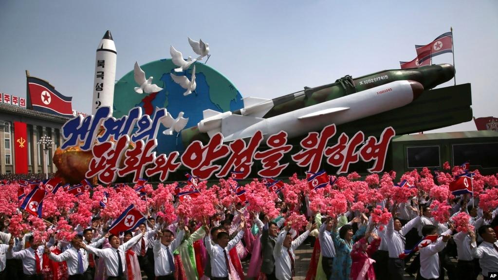 Dân Bắc Triều Tiên vẫy hoa, cờ trong lúc đoàn xe mang hình mẫu phi đạn và rocket đi ngang trong cuộc diễu hành tại Bình Nhưỡng 16/4/17