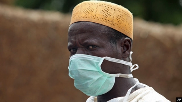 A local health worker wears a mask as he removes earth contaminated by lead from a family compound in the village of Dareta in Gusau, Nigeria, June 10, 2010.