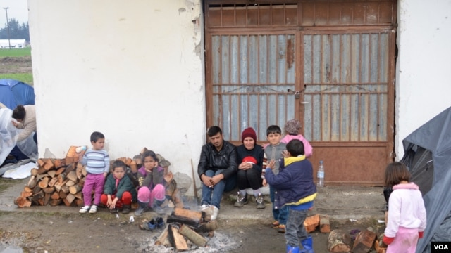 Refugee family attempts to stay warm not far from Macedonian border, in Idomeni, Greece, March 16, 2016. (J. Dettmer/VOA)