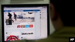 FILE - An Israeli soldier looks at the Facebook page of the Israel Defense Forces in Jerusalem, Nov. 15, 2012. Hostilities between Israel and the Palestinian group Hamas have found a battleground in social media.