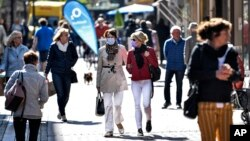 People walk in a shopping street in Gelsenkirchen, Germany, as many smaller stores are allowed to open on Monday, April 20, 2020. (AP Photo/Martin Meissner)