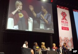 Graca Machel, right, wife of former president Nelson Mandela makes a point about the rights of young adolescent women as actress Charlize Theron looks on at the 2016 AIDS Conference in Durban, South Africa, July 19, 2016.
