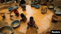 Des chercheurs de l'or tamisent la boue dans une nouvelle mine découverte dans une ferme de cacao près de la ville de Bouafle dans l'ouest de Côte-d'Ivoire, 18 mars 2014.
