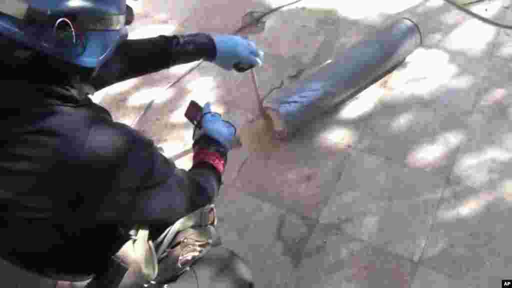 This image taken from amateur video posted online appears to show a presumed U.N. staff member measuring and photographing a canister in a Damascus suburb, August 26, 2013.