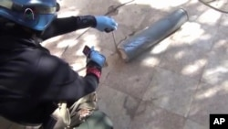 2013年8月26日联合国调查人员在大马士革一个郊区检查和拍摄一个榴弹的弹筒。