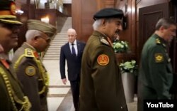 FILE - Yevgeny Prigozhin, background center, is seen at a meeting between Russian and Libyan military officials in Moscow, in a screengrab from footage published Nov. 7, 2018, by the self-styled Libyan National Army.