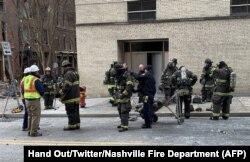 Dalam foto dari Twitter Departemen Pemadam Kebakaran Nashville, Petugas pemadam kebakaran berdiri di dekat kerusakan di jalan setelah ledakan di Nashville, Tennessee pada 25 Desember 2020. (Foto: AFP/HO/Twitter/Nshville Fire Department)