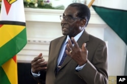 FILE - Zimbabwean President Robert Mugabe addresses his staff during a surprise birthday celebration event at State House in Harare, Feb. 22, 2016.