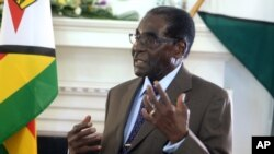 FILE - Zimbabwean President Robert Mugabe addresses his staff during a surprise birthday celebration event at State House in Harare, Feb. 22, 2016. Mugabe said Wednesday the country needs to rethink its indigenization policy.
