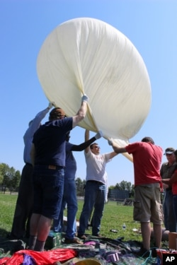 Students and faculty, including Mark Iewicz, center, a mechanical engineering student, prepare to test launch a camera-carrying balloon at the University of Hartford in West Hartford, Connecticut, Aug. 9, 2017.