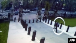 A close circuit video image shown during an Oct. 23, 2014 press conference at Royal Canadian Mounted Police headquarters in Ottawa shows supected shooter Michael Zehaf-Bibeau (circled) running towards the Canadian Parliament.