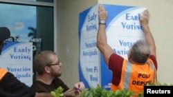 Petugas menempel poster mengenai pemilihan umum lebih awal di Miami-Dade, Florida (12/10). (AP/Lynne Sladky)