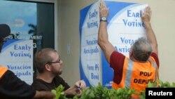 Des employés mettent des affiches dans les rues du comté de Miami-Dade pour annoncer le vote anticipé, le 12 octobre 2016.