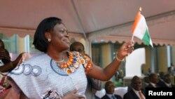 Simone Gbagbo, épouse du président Laurent Gbagbo, fait un geste de la main, tenant un drapelet lors de l'ouverture des célébrations marquant le 50ème anniversaire de l'indépendance de la Côte d'Ivoire
