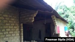 Un homme assiste impuissant à l'écroulement de sa maison Bégoua, le 27 août 2017. (VOA/Freeman Sipila)