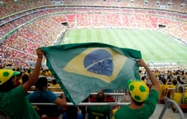Fans hold a Brazilian flag before the Confederations Cup Group A soccer match between Brazil and Japan, June 15, 2013.