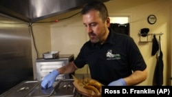 In this Thursday, October 10, 2019 photo, Jose Gamiz, a co-owner at the Mi Vegana Madre restaurant, prepares fresh vegan tacos in Glendale, Arizona.