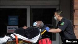 Seorang paramedik membawa pasien ke unit gawat darurat RS Maimonides di tengah wabah virus corona di Brooklyn, New York, 7 April 2020. (Foto: Reuters)