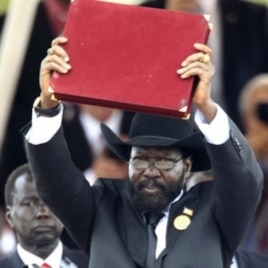 South Sudan's President Salva Kiir displays the transitional constitution of the Republic of South Sudan after signing it into law during the Independence Day celebrations in the capital Juba, July 9, 2011