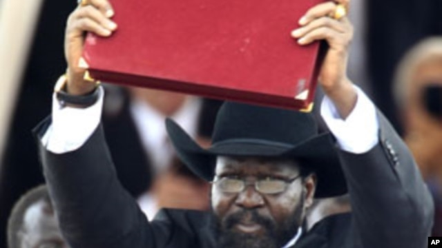 South Sudan's President Salva Kiir displays the transitional constitution of the Republic of South Sudan after signing it into law during the Independence Day celebrations in the capital Juba, July 9, 2011.