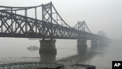 FILE - Trucks move across the bridge linking North Korea with the Chinese border city of Dandong, March 3, 2016. China in April banned imports of gold and rare earths from North Korea, as well as fuel jet exports.