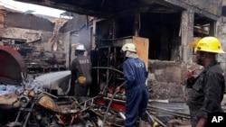 Des pompiers se battent pour éteindre le feu d'un incendie après une explosion à Accra, Ghana, 4 juin 2015.