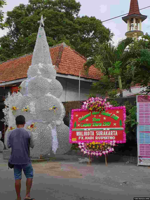 Pohon Natal setinggi 6 meter dari 9.000 botol plastik bekas kemasan air mineral terpajang di depan Gereja Santa Perawan Maria Regina Purbowardayan, Solo, 24 Desember 2018. (Foto: Yudha Satriawan/VOA)