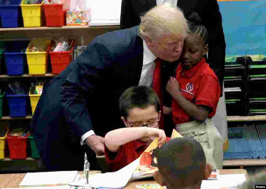 Republican presidential nominee Donald Trump hugs a student after receiving a bible as a gift during a campaign visit to the International Church of Las Vegas and the International Christian Academy in Las Vegas, Nevada, Oct. 5, 2016.