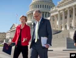 FILE - Senator Elizabeth Warren, D-Mass., left, and Senate Minority Leader Chuck Schumer, D-N.Y., walk to a news conference at the Capitol in Washington, Wednesday, Oct. 18, 2017.