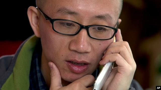 FILE - Chinese dissident Hu Jia talks on his phone during a meeting at a restaurant in Beijing, April 10, 2013.