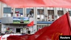 Những người biểu tình thân Nga đứng tại văn phòng dịch vụ an ninh quốc gia SBU bị chiếm ở Luhansk, miền đông Ukraine, 18/4/2014.