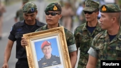 An honor guard hold up a picture of Samarn Poonan, 38, a former member of Thailand's elite navy SEAL unit who died working to save 12 boys and their soccer coach trapped inside a flooded cave as family members weep at a airport, in Rayong province, Thailand, July 6, 2018.
