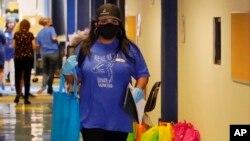 Učiteljica Najeli Koronado u osnovnoj školi u Oklahomi nosi torbu sa školskim priborom i ajped za jednog od svojih đaka. Škola daje elektronske uređaje svim učenicima.