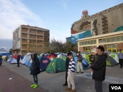Thousands of refugees are living in tents and converted warehouses at Piraeus port, Athens. (Henry Ridgwell/VOA)