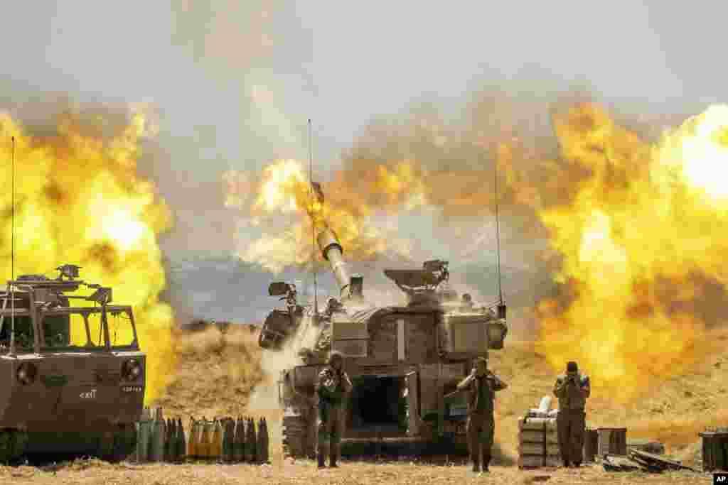 An Israeli artillery unit fires toward targets in Gaza Strip, at the Israeli Gaza border.