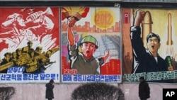 FILE - Pyongyang residents walk past posters with popular slogans illustrating North Korea's main policies.