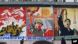 FILE - Residents walk past posters with popular slogans illustrating North Korea's main policies, on a street in Pyongyang, North Korea.