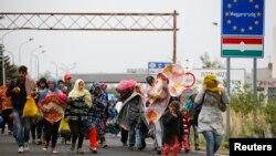 Para migran berjalan melintasi perbatasan dari Hungaria ke Nickelsdorf, Austria, 25 September 2015 (Foto: dok).