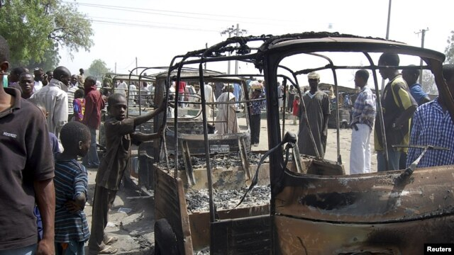 Residents survey vehicles damaged after a bomb blast at a primary school in Maiduguri, capital of Borno state, February 29, 2012.