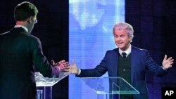 Right-wing populist leader Geert Wilders gestures as he talks to Dutch Prime Minister Mark Rutte, left, during a national televised debate, the first head-to-head meeting of the two political party leaders since the start of the election campaign, at Erasmus University in Rotterdam, Netherlands, March 13, 2017.