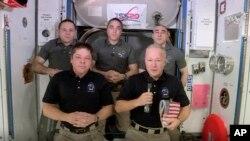 Wawili mstari wa mbele, kutoka kushoto, wanaanga Bob Behnken na Doug Hurley wakati wa mazungumzo na NASA wakiwa katika kituo cha anga za juu cha kimataifa Jumamosi Agosti 1, 2020.