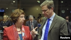European Union foreign policy chief Catherine Ashton talks with German Foreign Minister Guido Westerwelle at the start of a European Union foreign ministers meeting at the EU Council in Brussels, December 10, 2012.