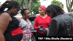 Female taxi drivers Julie Wahome, Lydia Muchiri, Faridah Khamis and Agnes Mwongara chat at a parking lot in Nairobi, April 19, 2018.