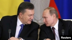 Russia's President Vladimir Putin (R) looks at his Ukrainian counterpart Viktor Yanukovich during a signing ceremony after a meeting of the Russian-Ukrainian Interstate Commission at the Kremlin in Moscow, Dec. 17, 2013.