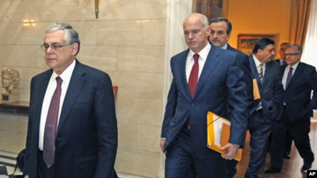 Greece's Prime Minister Lucas Papademos (L) escorts Socialist leader George Papandreou (C), conservative party leader Antonis Samaras (3rd L) and Far-right leader George Karatzaferis (2nd R) at his office in Athens, February 8, 2012.