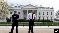 Members of the Secret Service stand outside the White House, April 7, 2015.