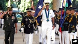 In this photo released by Public Affaires Office, Armed Forces of the Philippines, U.S. Adm. Samuel J. Locklear, third from left, commander of the U.S. Pacific Command, accompanied by Philippine Armed Forces Chief Gen. Gregorio Pio Catapang, left, salutes the colors during arrival honors, Oct. 14, 2014, at Camp Aguinaldo General Headquarters at suburban Quezon city northeast of Manila.