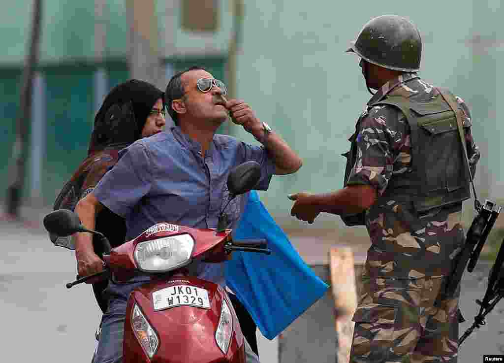 A man shows his tooth to an Indian policemen as he seeks permission to see a doctor after he was stopped during a curfew in Srinagar.